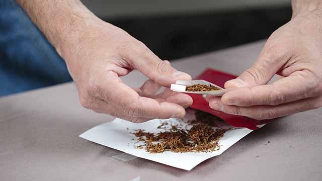 Tabak wird zu einer Zigarette gedreht