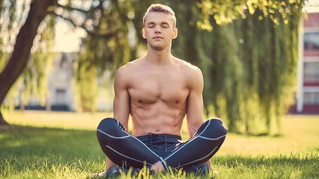Mann meditiert im Park