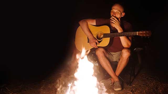 Mann raucht Kräuterzigarette am Lagerfeuer